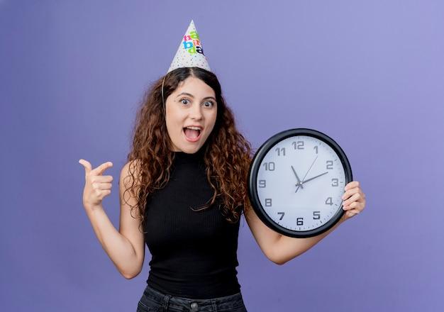 Junge schöne frau mit dem lockigen haar in einer feiertagsmütze, die wanduhr hält, die fröhlich geburtstagsfeierkonzept steht, das über blaue wand steht Kostenlose Fotos