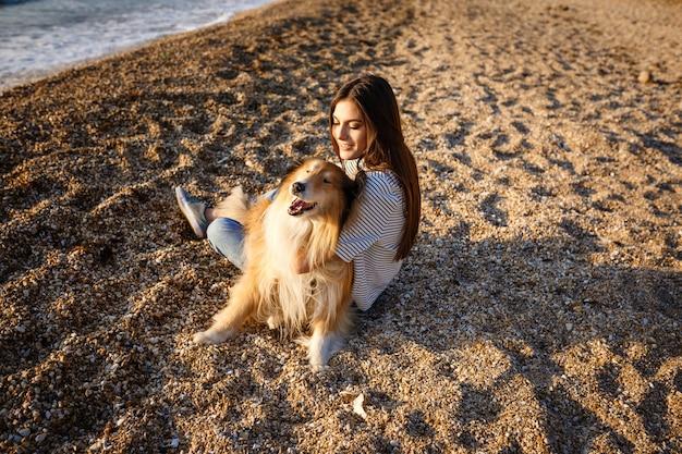Junge schöne frau mit langen haaren, die mit colliehund gehen. draußen im park. in der nähe des meeres, sommer beatch Premium Fotos