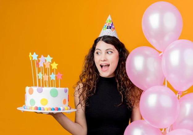 Junge schöne frau mit lockigem haar in einer feiertagskappe, die luftballons und geburtstagskuchen-glückliches und aufgeregtes geburtstagsfeierkonzept hält, das über orange wand steht Kostenlose Fotos