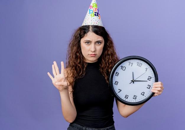 Junge schöne frau mit lockigem haar in einer feiertagskappe, die wanduhr hält, die nummer vier mit traurigem ausdruck geburtstagsfeierkonzept steht, das über blauer wand steht Kostenlose Fotos