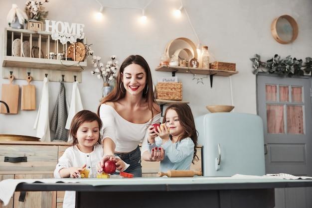 Junge schöne frau zieht zwei kinder mit äpfeln ein, während sie nahe der tabelle mit spielwaren sitzen Premium Fotos