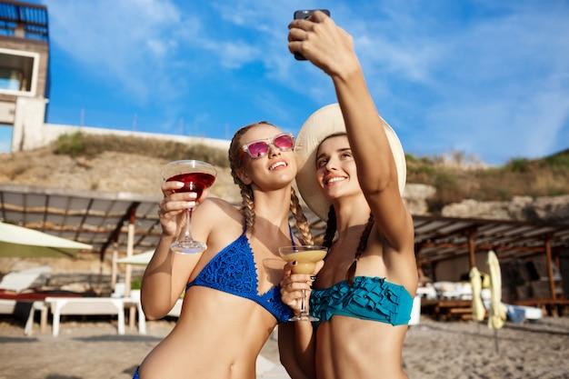 Junge schöne frauen in der badebekleidung lächelnd, selfie am strand machend Kostenlose Fotos