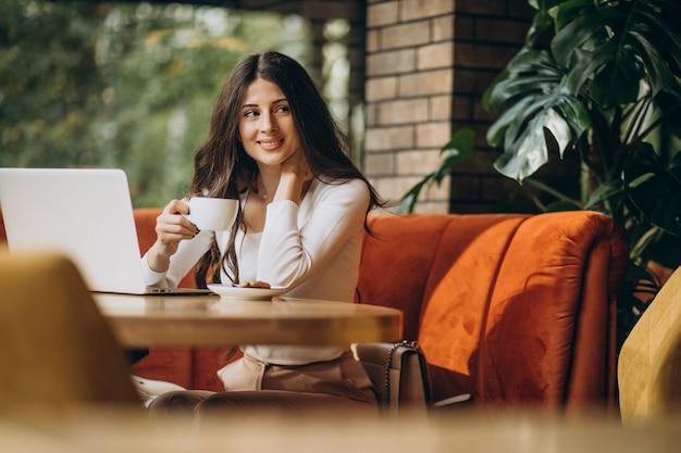 Junge schöne geschäftsfrau, die am computer in einem café arbeitet Kostenlose Fotos