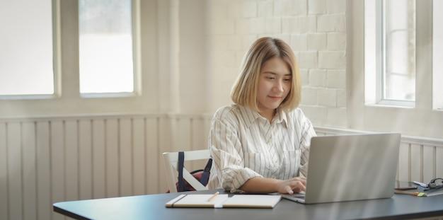 Junge schöne geschäftsfrau, die auf laptop-computer schreibt Premium Fotos
