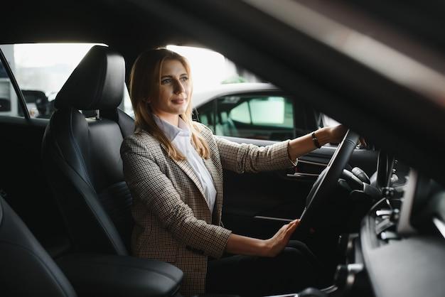 Junge schöne geschäftsfrau, die in ihrem auto sitzt Premium Fotos