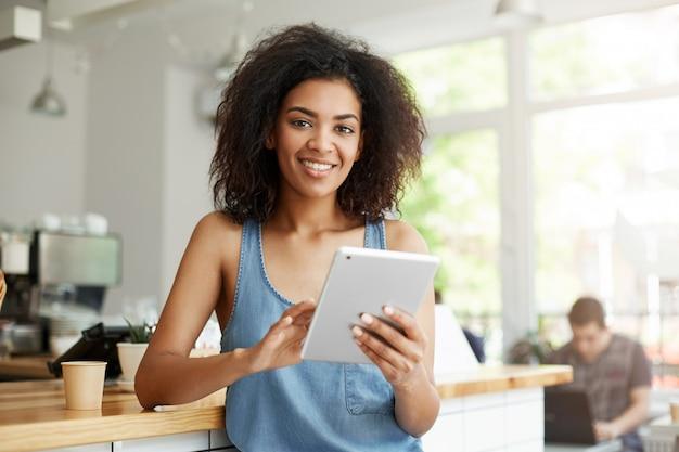 Junge schöne glückliche afrikanische frau, die im café lächelnd hält tablette ruht. Kostenlose Fotos