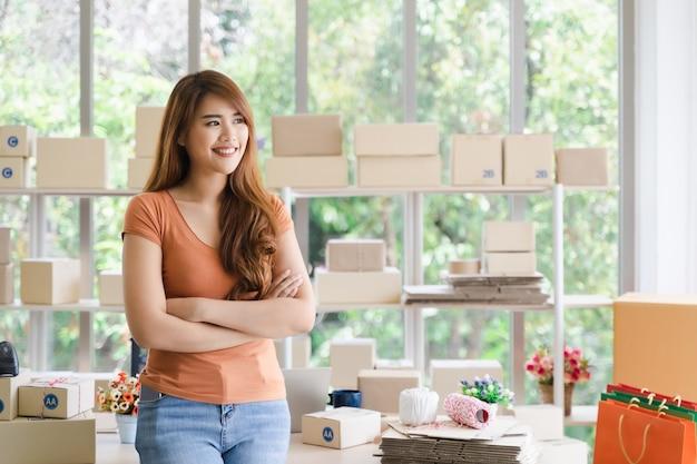 Junge schöne glückliche asiatische erfolgreiche geschäftsfrau mit smiley steht mit den armen, die in ihrem startinnenministerium, frau im guten gefühl mit geschäftserfolg, lieferungsverkäuferkonzept gekreuzt werden Premium Fotos