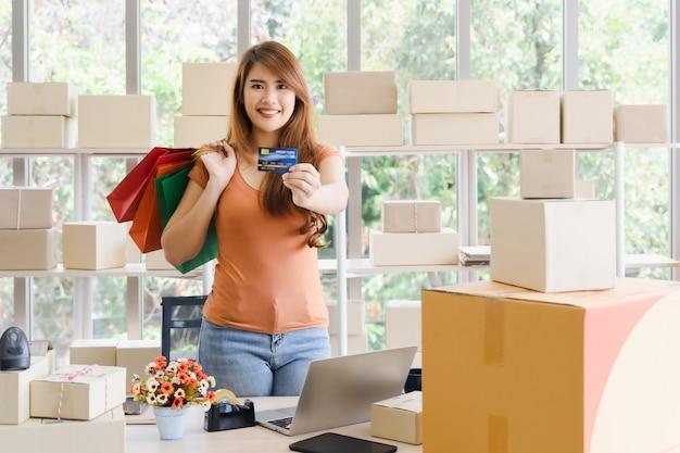 Junge schöne glückliche asiatische geschäftsfrau mit smiley zeigt kreditkarte oder debitkarte Premium Fotos
