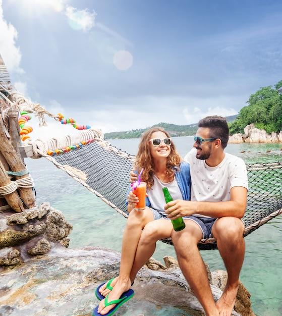 Junge schöne glückliche lächelnde lustige paare ein mann und beste freunde einer frau auf einer hängematte trinken im urlaub auffrischungsgetränke Premium Fotos