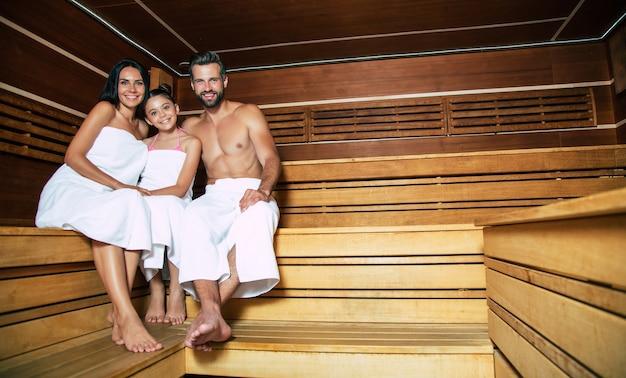 Junge schöne glückliche vater und mutter mit kleiner süßer tochter in den badetüchern entspannen in der heißen sauna Premium Fotos
