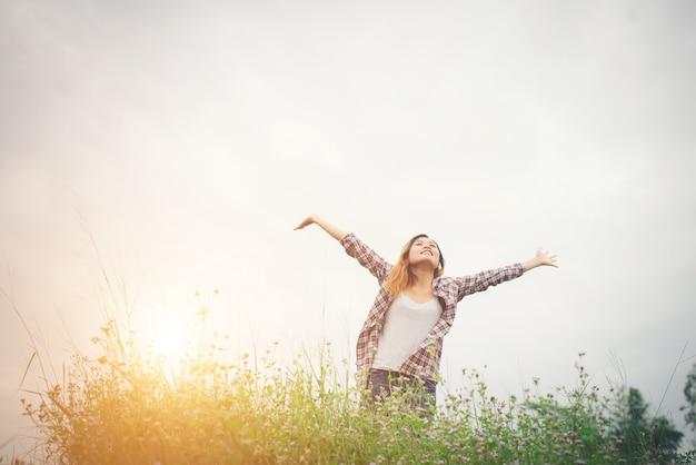 Junge schöne hippie-frau, die in einem blumenfeld bei sonnenuntergang. befreit Kostenlose Fotos