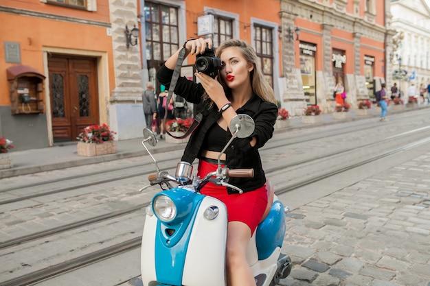 Junge schöne hipsterfrau, die mit fotokamera auf motorradstadtstraße reitet Kostenlose Fotos