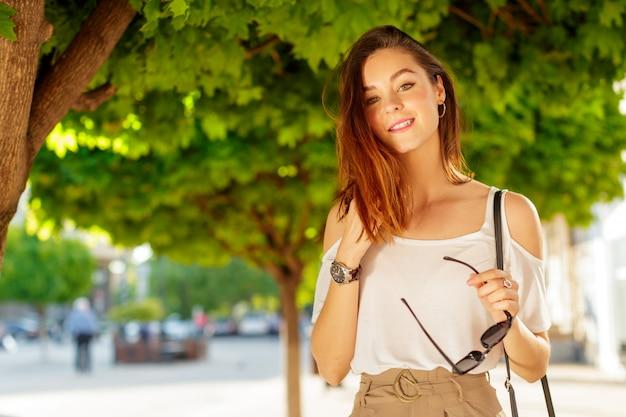 Junge schöne kaukasische frauenaufstellung im freien in der stadt Premium Fotos