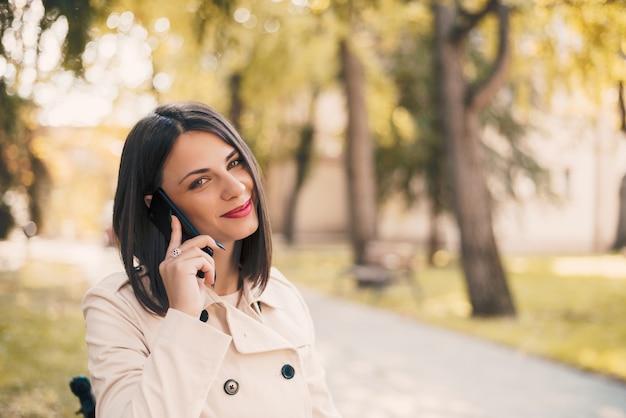 Junge schöne lächelnde frau, die am handy im park spricht. Premium Fotos