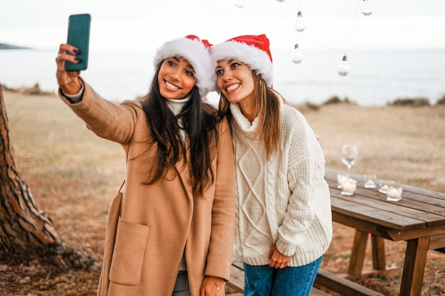 Junge schöne lächelnde freundinnen der gemischten rasse, die ein selbstporträt machen, das ihr telefon im freien mit weihnachtsmannhut betrachtet Premium Fotos