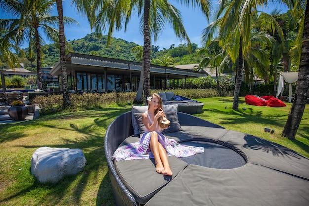 Junge schöne lächelnde kokosnuss haltene und entspannende frau Premium Fotos