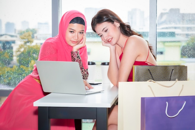 Junge schöne moslemische frau und kaukasische freundschaften mit einkaufstaschen und tablette genießend beim einkauf an der kaffeestube Premium Fotos