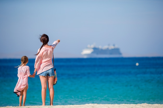 Junge schöne mutter und ihre entzückende kleine tochter am tropischen strand, der das meer betrachtet Premium Fotos