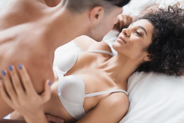 Junge schöne paare in der unterwäsche, die auf bett liegt Premium Fotos