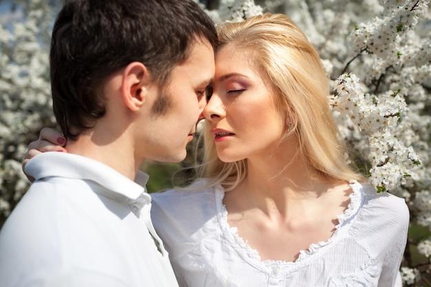Junge schöne paarfrau und -mann, die einander über blühenden fröhlichen baumhintergrund an klarem sonnigem tag küssen Premium Fotos