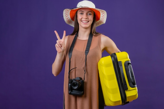 Junge schöne reisende frau im sommerhut mit gelbem koffer und kamera positiv und glücklich lächelnd fröhlich siegreiches zeichen oder nummer zwei stehend über lila hintergrund Kostenlose Fotos