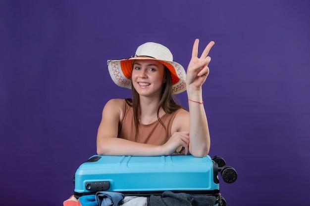 Junge schöne reisende frau im sommerhut mit koffer voller kleidung positiv und glücklich lächelnd fröhlich optimistisch zeigt siegeszeichen oder nummer zwei über lila wand Kostenlose Fotos