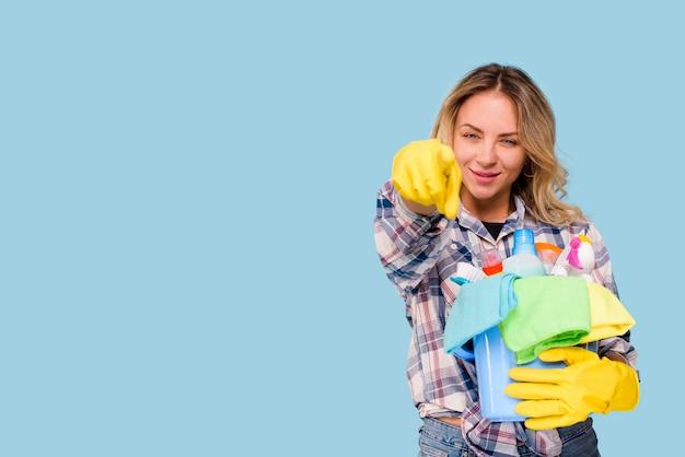 Junge schöne sauberere frau, die eimer mit den produkten zeigen auf kamera gegen blauen hintergrund hält Kostenlose Fotos