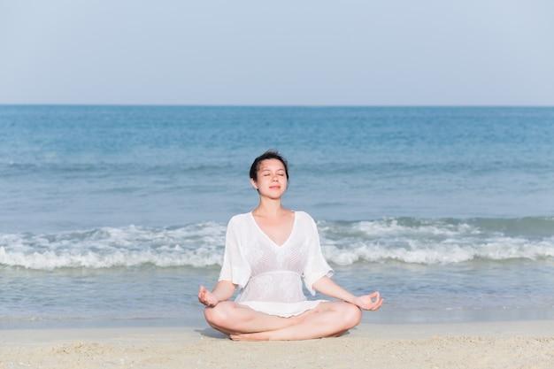 Junge schöne schwangere frau im weißen kleid, das yoga tut, trainiert Premium Fotos