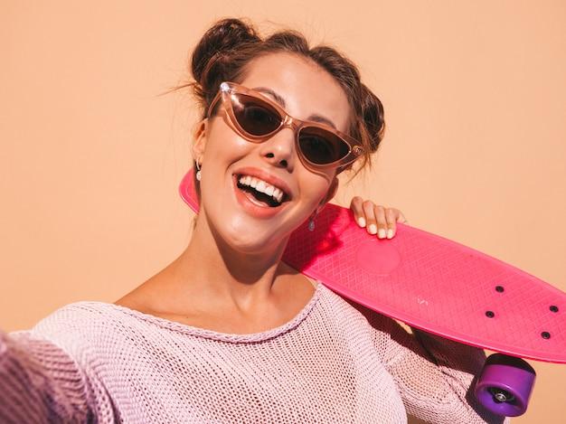 Junge schöne sexy lächelnde hippie-frau in der sonnenbrille trendy mädchen in sommer gestrickter wolljacke frau mit dem rosa pennyskateboard, lokalisiert auf beige wand nehmen von selfie selbstporträtfotos auf phon Kostenlose Fotos