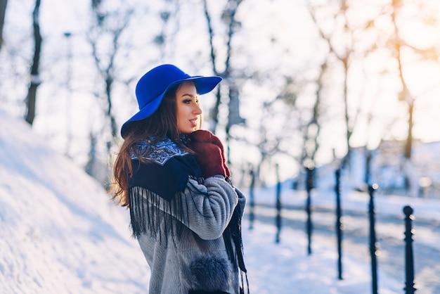 Junge schöne stilvolle frau mit perfektem lächeln im blauen hut und im schal gehend hinunter die straße Premium Fotos