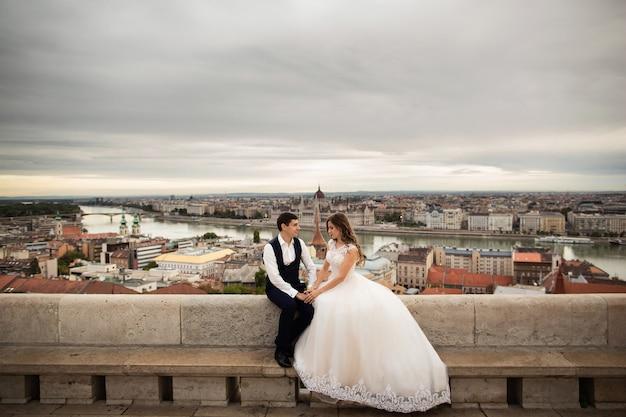 Junge schöne stilvolle paare jungvermählten, die durch die fischerbastei in budapest, ungarn sitzen Premium Fotos