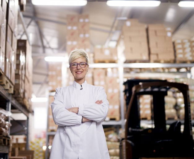 Junge schöne stolze arbeiterin hält ihre arme verschränkt und lächelt für die kamera neben dem gabelstapler in einem fabriklagerraum. Premium Fotos
