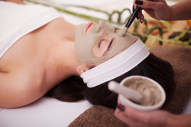 Junge, schöne und gesunde frau im badekurortsalon. traditionelle orientalische massagetherapie und schönheitsbehandlungen. Premium Fotos