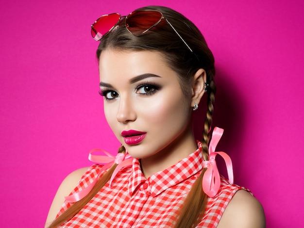 Junge schöne verspielte frau schaut über ihre herzförmige rote brille. valentinstag, liebe oder pinup thema party konzept. smokey augen und rote lippen make-up. Premium Fotos