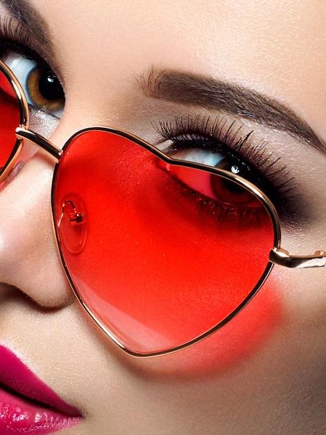 Junge schöne verspielte frau schaut über ihre herzförmige rote brille. valentinstag, liebe oder thema party konzept. smokey augen und rote lippen make-up. Premium Fotos