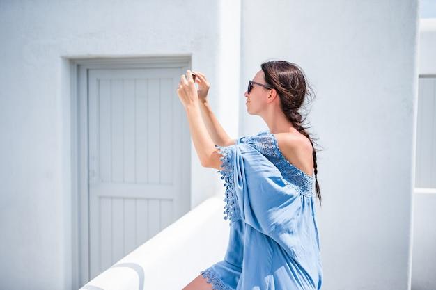 Junge schönheit, die draußen selfie mit telefon während der ferien nimmt Premium Fotos
