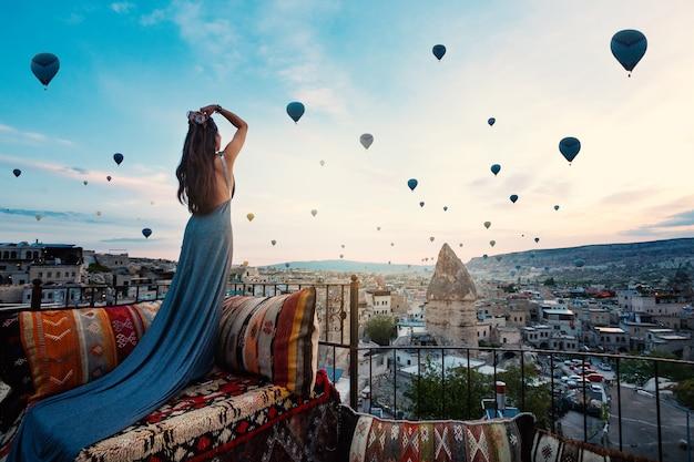 Junge schönheit, die elegantes langes kleid vor cappadocia-landschaft am sonnenschein mit ballonen in der luft trägt. truthahn. Premium Fotos