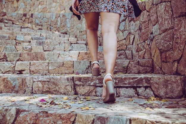 Junge schönheit, die herauf die steintreppe mit hintergrund geht. schritt für erfolgskonzept. Premium Fotos