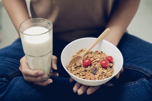 Junge schönheit mach s gut ihre gesundheit, indem sie milch mit granola mit mehreren körnern am morgen isst Premium Fotos