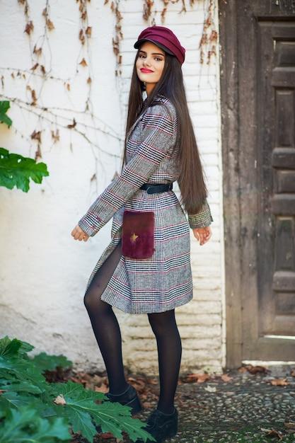 Junge schönheit mit tragendem wintermantel und kappe des sehr langen haares im herbstlaubhintergrund Premium Fotos