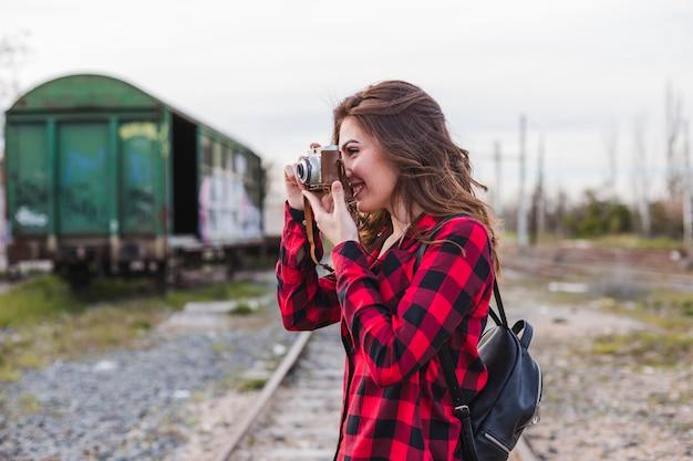 Junge schönheit, welche die zufällige kleidung macht ein foto mit einer weinlesekamera trägt. Premium Fotos