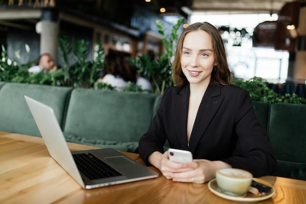 Junge schönheitsfrau, die am laptop im kaffeehaus arbeitet Kostenlose Fotos