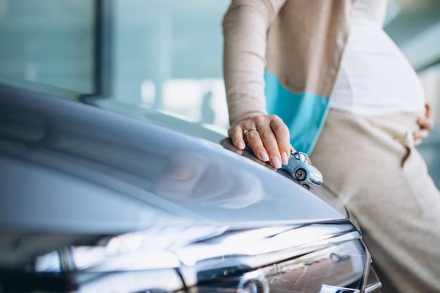 Junge schwangere frau, die ein auto in einem autoausstellungsraum wählt Kostenlose Fotos