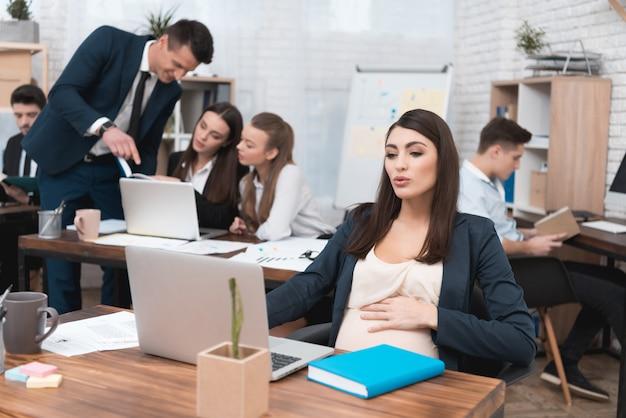 Junge schwangere geschäftsfrau, die im büro arbeitet Premium Fotos