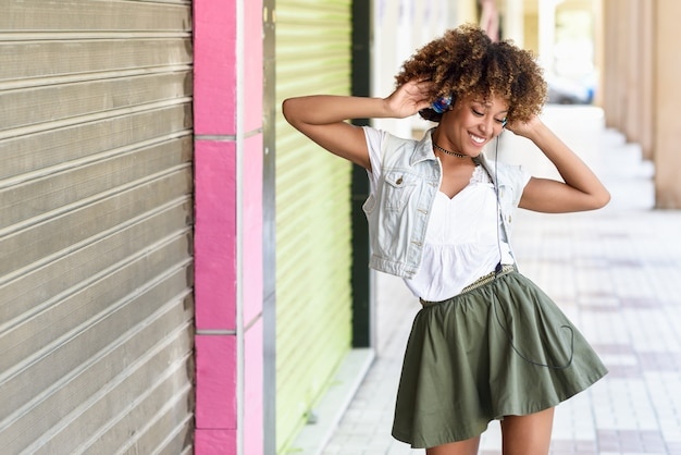 Junge schwarze frau, afrofrisur, in der städtischen straße mit kopfhörern Premium Fotos