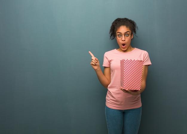 Junge schwarze frau, die auf die seite zeigt. sie hält einen popcorn-eimer in der hand. Premium Fotos