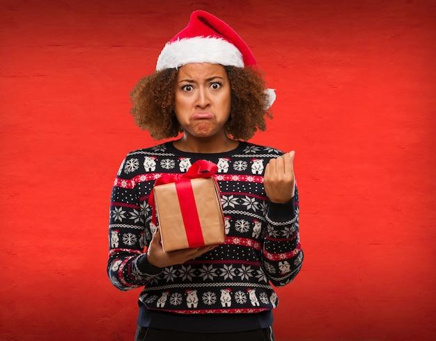 Junge schwarze frau, die ein geschenk am weihnachtstag eine geste des bedarfs tuend anhält Premium Fotos