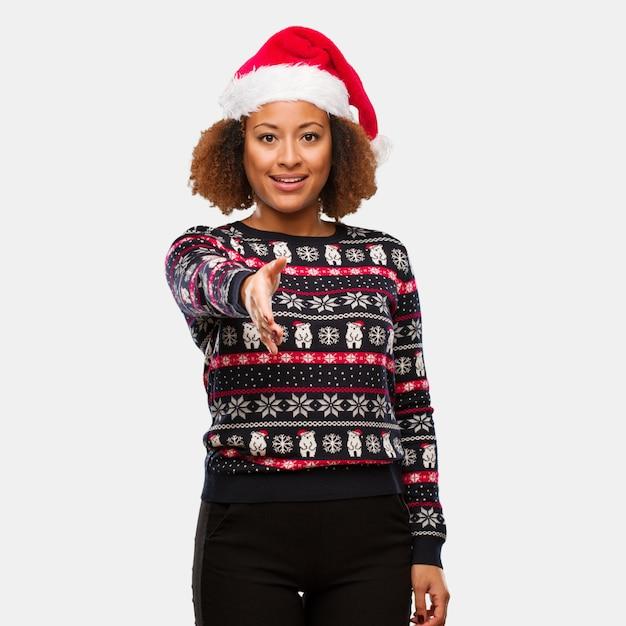 Junge schwarze frau in einer modischen weihnachtsstrickjacke mit dem druck, der heraus erreicht, um jemand zu grüßen Premium Fotos