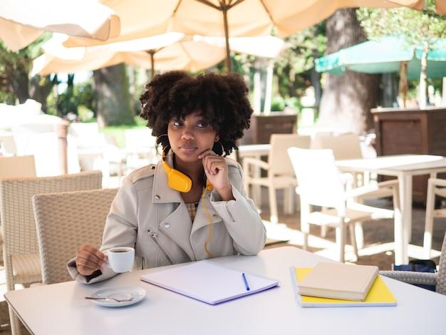 Junge schwarze frau saß an einem tisch in einem café, während sie draußen papierkram erledigte Premium Fotos