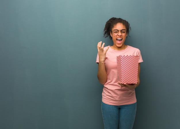 Junge schwarze frau sehr ängstlich und ängstlich sie hält einen popcorneimer Premium Fotos